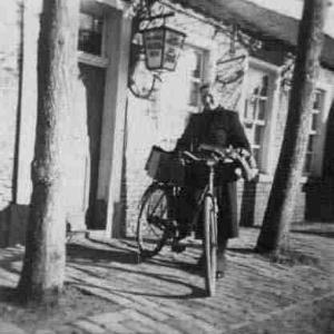 """Ab und zu kam es vor, daß auch Henriette Meinders aufs Rad mußte, um noch eilige Sendungen wegzubringen. In der Lampe kann man den Namen """"Schankwirtschaft zur Post"""" lesen."""